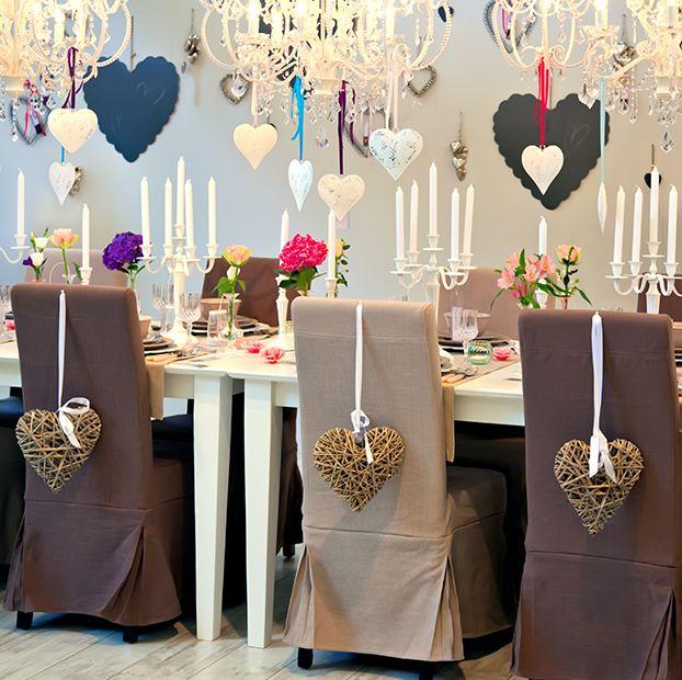 Sala decorada para festa de final de ano. Mesa de Natal ou Decoração de Ano Novo. Decoração romântica com candelabros, enfeites de coração e cores delicadas.
