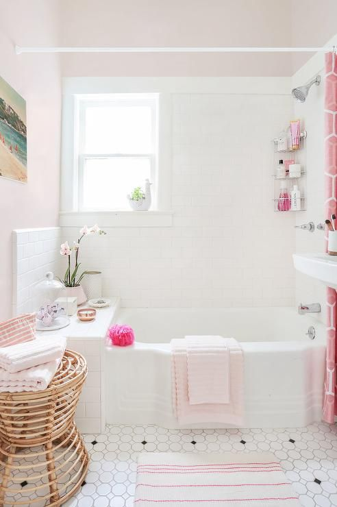 Pink, girly bathroom features a vintage drop-in tub accented with white subway tiles finished with a pink geometric shower curtain as well as a pink bath mat.