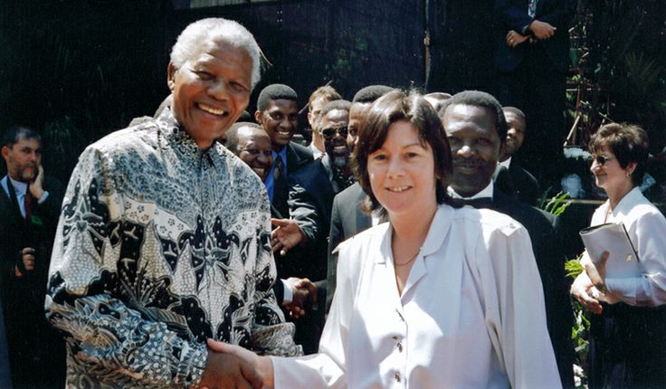 This picture was taken by Tokyo Sexwale at the Braamfontein Cemetery on September 24 1996 on the occasion of the unveiling of the memorial to Enoch Sontonga.  I was part of the massed choirs, and at the end of the concert, Mandela asked if he could meet everyone of the orchestra and massed choirs.  In the picture is also John Kani who was the MOC of the event. Submitted by Carol Baird