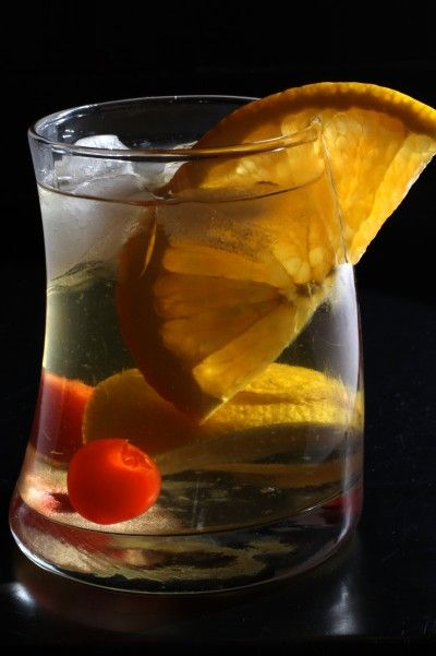 Old Fashioned Mixed Drink Whisky, Maraschino Cherry, Lemon wedge, Orange slice, Sugar cube and Bitters.