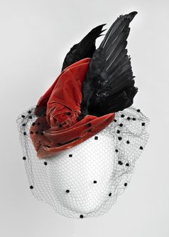 1945-50. A coral red velvet pillar box with small shaped rim in the style of a 19th century riding hat by Otto Lucas. The black net veil has tiny tufts of soft black 'fur' dotted throughout and this can be worn upon the black wings and velvet decoration or covering the face. The hat was provided with matching hatpins, there ends made of small velvet balls.