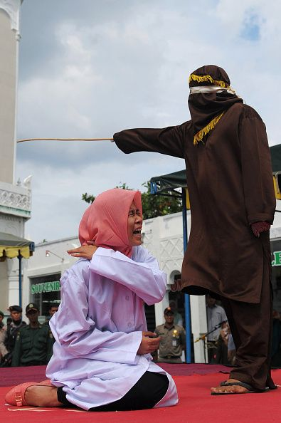 """Officials in Banda Aceh, Indonesia, held a public caning Monday. According to the Jakarta Post, six people were brutally beaten outside a mosque for indecency and gambling, activities prohibited by the province of Aceh's Islamic bylaws, or """"qanun.""""  Among the guilty were two university students, a man, 23,..."""