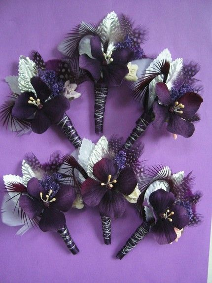 "made with dark purple hydrangea blossom with ivory stamens, white and silver millinery leaves, purple guinea feathers, lavender and dark fuschia marabou feathers, small clay flowers, dark purple goose biot feather loops, purple preserved candytuft, and the stems have been wrapped with a dark purple ribbon with silver metallic floss wrapped around. The groom's boutonniere has a touch of pink to stand out from the rest. These are 4-4.5"" long."