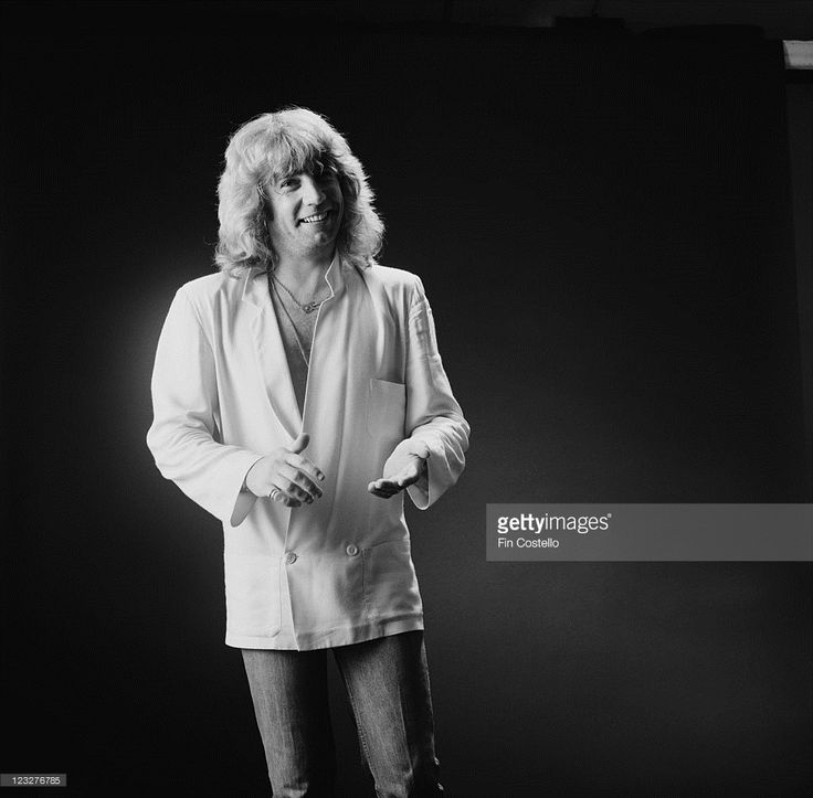 Rick Parfitt, guitarist with British rock band Status Quo, wearing a white jacket in a studio portrait, against a dark background, United Kingdom, in September 1979.