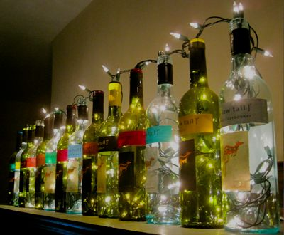 add a few string lights to your pretty wine bottles to brighten up your holiday decor - Decorate College Apartment