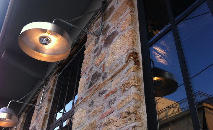Μεταλλικά φωτιστικά εξωτερικού χώρου με λάμπες καθρέπτη σε πέτρινο café. Δείτε περισσότερα έργα μας στο  http://www.artease.gr/interior-design/emporikoi-xoroi/
