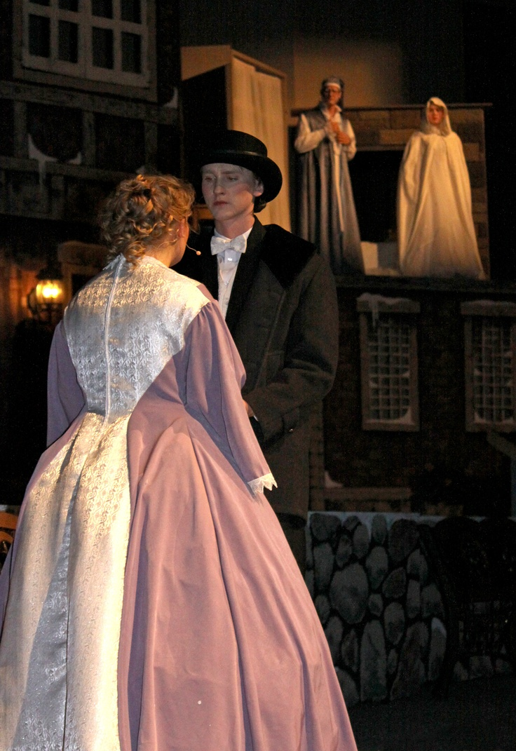 Ebenezer, played by Joseph Wilson and the ghost of Christmas past, played by Madison Wagner-Powers, watch in the background as Belle, played by Kristi Kozun, breaks up with the young Ebenezer, played by Tanner Kooistra. Photo by Fiona Graham — at Briercrest College and Seminary.
