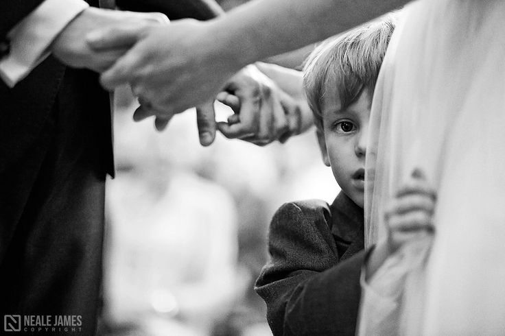 A bride's son holds her tightly and peeks around her dress as she holds her groom hands. Black and white wedding photography via nealejames.com