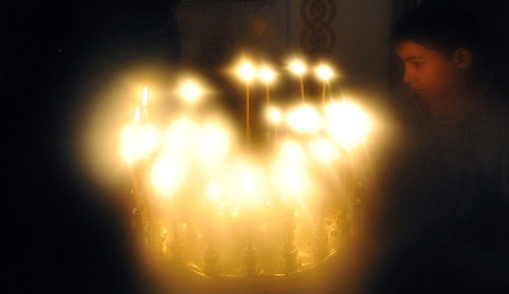 Kyrgyzstan, A boy lights a candle during an Orthodox Christmas service in a church in Bishkek on January 6, 2012