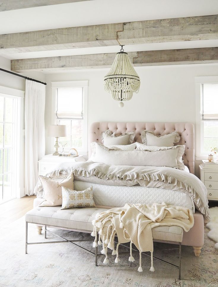 blush pink touches in bedroom with rustic beams and chandelier