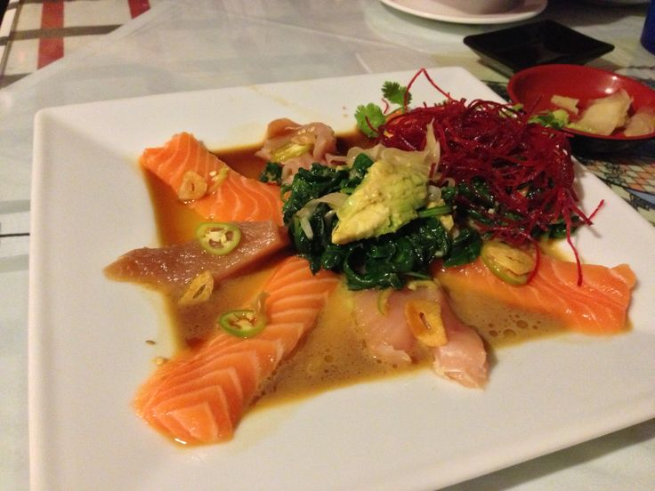 Salmon and Tuna sashimi appetizer, with view of avocado, onions, and garlic inside the spinach