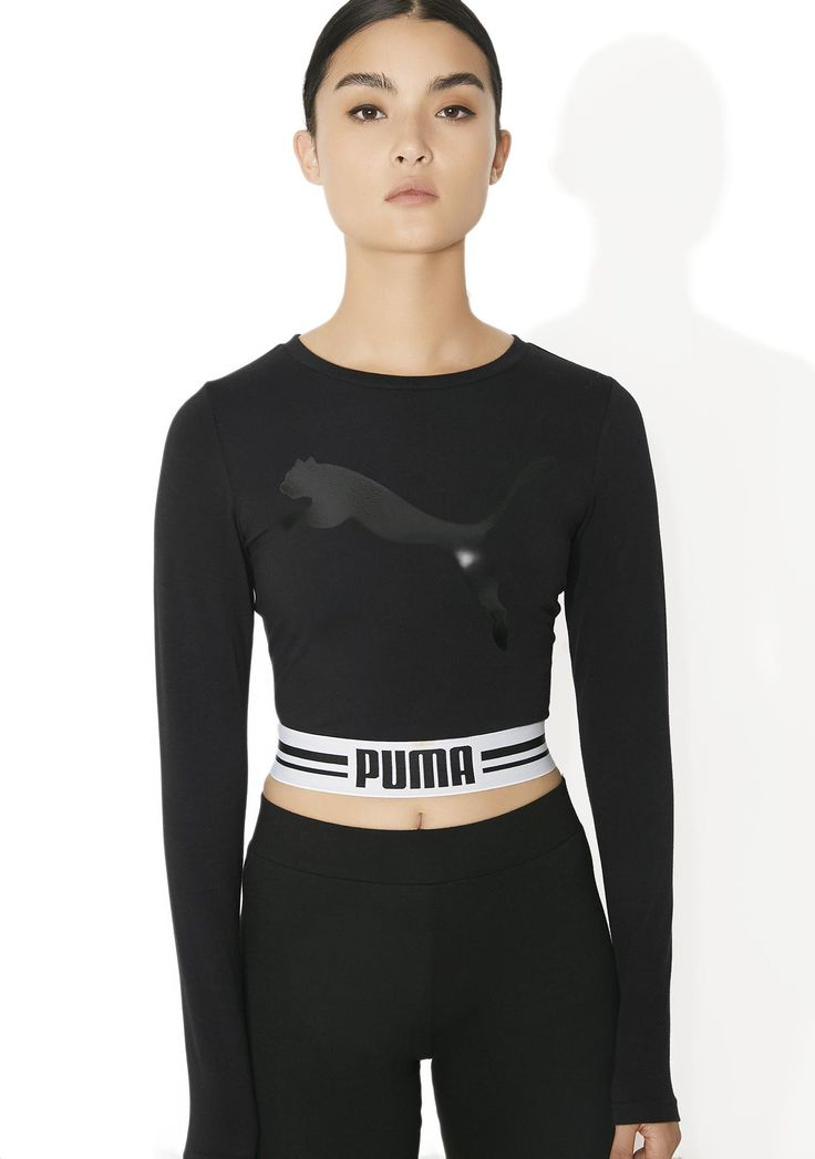 "PUMA Fly Cat Long Sleeve Cropped Tee cuz yew know yew stay lookin' good, babe. Sass 'em in this top features a slim fitting black construction, long sleeves, round neckline, a shiny black cat leapin' across yer chest, and a stretchy banded bottom with black ""PUMA"" text on da front."