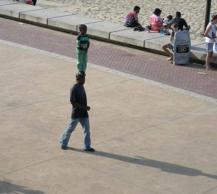 A man walking down the street with his son standing on his head (Durban, South Africa)