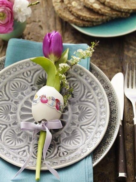 Hier wird bei Tellern, Servietten und Blumen mit Kontrasten dekoriert - trotzdem entsteht Harmonie bei dieser Tischdeko zu Ostern.