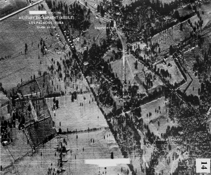 October 14, 1962: This photograph is taken by a U-2 flying over Cuba. Analyzed by the CIA the next day, the photo shows a truck convoy approaching Soviet medium-range ballistic missile (MRBMs). It is the first photo identified as showing Soviet MRBMs in Cuba. Source: Dino A. Brugioni collection, National Security Archive
