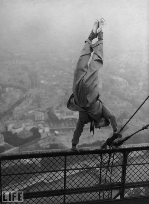 Crazy ~ Circa 1935, a dapper daredevil balances on a handrail at the top of the Eiffel Tower in Paris.