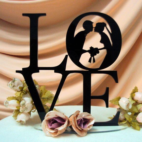 O Topo de bolo silhueta Love Casal com Buquê vai levar todo o romantismo para a decoração do seu casamento. Este topo de bolo é um mimo à parte na decoração seja em uma festa, chá da noiva e até mesmo como uma decoração em casa. informações sobre o produto: Material: Acrílico preto, branco, dourado, pink ou roxo Medidas: 15cm de comprimento X 15 cm de altura . A espessura é de 3mm Importante: Todo topo de bolo silhueta vem em uma base de acrílico transparente, podendo ser colocado em qua…
