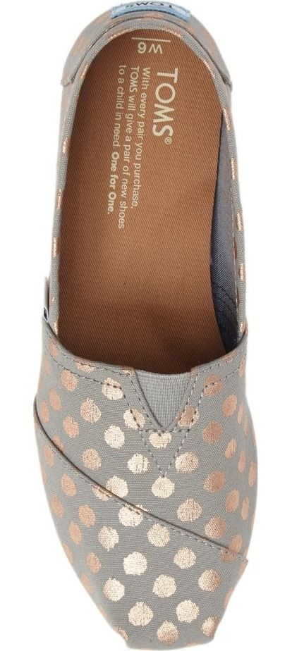Decorated with shimmery polka dots, these casual, comfortable slip-ons feature TOMS' signature center goring panel and asymmetrical toe cap.