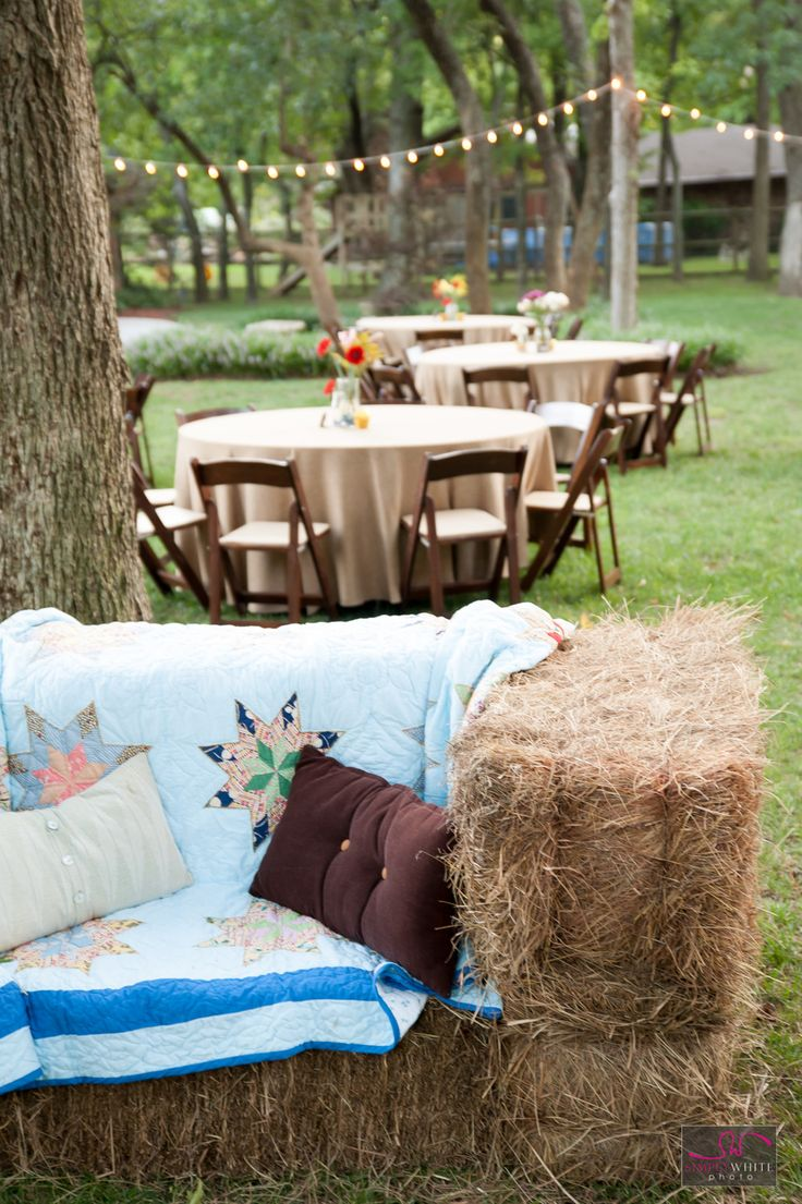 Cute backyard wedding reception. With hay bale couches, twinkly lights, picnic wedding reception.