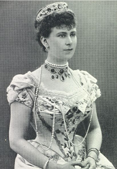 Princess Mary of Teck , as she was when she married Prince George of York in 1893. Wearing the 'Kent Amethyst Parure', passed down from Queen Victoria's mother, the then Duchess of Kent, (rather than the current holder of that title). The tiara is designed as a series of larger and smaller amethyst ovals, set both vertically and horizontally, each surrounded by diamonds and within bands of diamonds top and bottom.