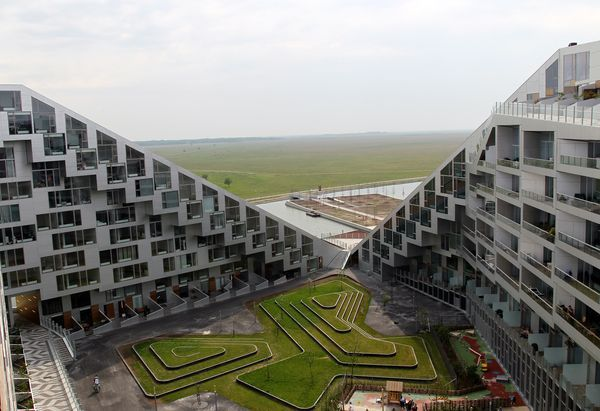 Designed by the Bjarke Ingels Group, the suburban housing development—about a ten-minute train ride outside of Copenhagen—has nearly 500 apartments and incorporates a commercial district, so that residents don't need to burn fossil fuels to shop for groceries or lounge at a cafe.    The buildings, officially opened in 2010, are oriented to capture as much daylight as possible, and an elaborate 18,000-square-foot green roof helps to deflect harsh rays and keep the grounds cool.