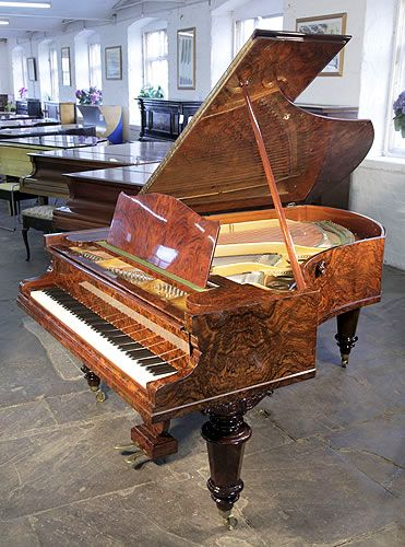 An 1882, Bechstein Model V grand piano for sale with a book matched, burr walnut case and turned legs at Besbrode Pianos £18,000. Piano hasan eighty-eight note keyboard and a two-pedal lyre.