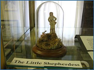 "Ma's China Shepheress: This figurine was found among Carrie's things in Keystone, SD. The foot had been broken and mended with sealing wax, evidence that it had been cherished. Later, William Anderson found a letter that Laura had written to some school children. In it she wrote, ""Carrie has the little shepherdess."" We feel confident that this is the figure that the family had treasured."