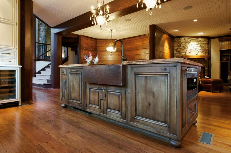 This inviting, open plan kitchen features all-over wood accents, including wall paneling, a white beadboard ceiling and dark exposed beams. The kitchen island boasts a rustic vibe with its warm brown cabinets and hammered copper farmhouse sink.