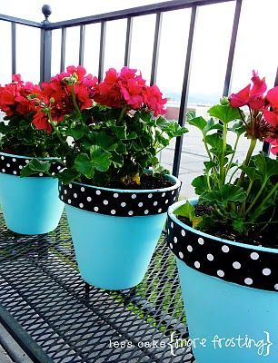 Painted terra cotta pots (in wedding colors) with flowers as centerpieces.: