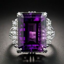 A rich royal purple emerald-cut Amethyst, weighing 14.12 carats, and measuring 5/8 inch long, is tastefully and sturdily presented in platinum between vertical rows of small sparkling round brilliant-cut diamonds on the shoulders finished with a decorative open scroll design on the side gallery. A striking, statement making cocktail ring. Currently ring size 5 1/2.