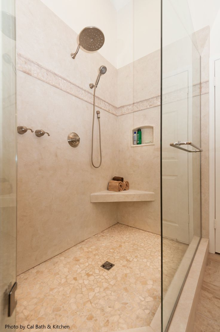 Big transitional shower with a corner shower bench, pebble tile inlay, travertine all around and a rain water shower head. Now, see 11 other awesome shower heads perfect for your master bathroom.