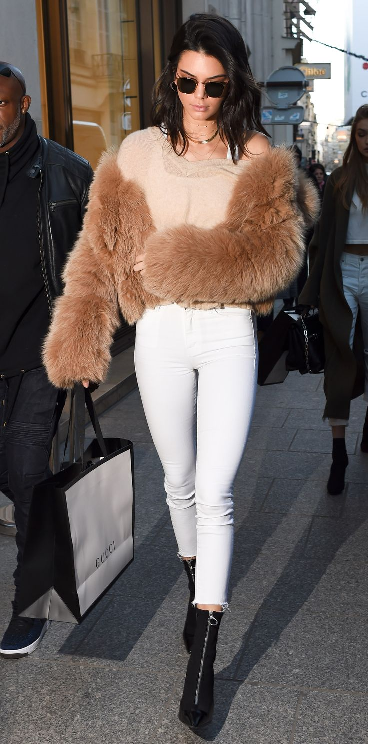 The Victoria's Secret model donned a sheer top, white jeans, and a fur topper for a shopping trip to Gucci while in Paris for the 2016 Victoria's Secret Fashion Show. She accessorized with zip-up black boots, dark shades, and layered necklaces for the overseas excursion.