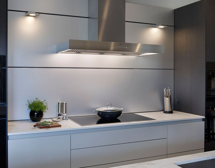 'Natural' aluminium wall panels reflect the LED spotlight illumination and create a sleek finish behind the Miele induction cooktop. Either side of the hob areas of worktop provide space for preparation and cooking utensils. Below the hob, a mixture of 'grip rail' and 'touch to open' drawers and cupboards house pots and pans. #inductionhob #Miele #extractorhood #Gaggenau #bulthaupkitchen