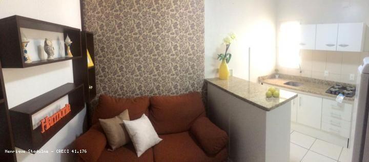 Sala de estar e cozinha com balcão americano em apartamento kitnet.