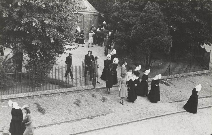 Kerkgang te Huizen. De kerk gaat uit. Mannen en vrouwen, in zowel streekdracht als modekleding, verlaten de kerk. 1945 #NoordHolland #Huizen #isabee #oorijzermuts