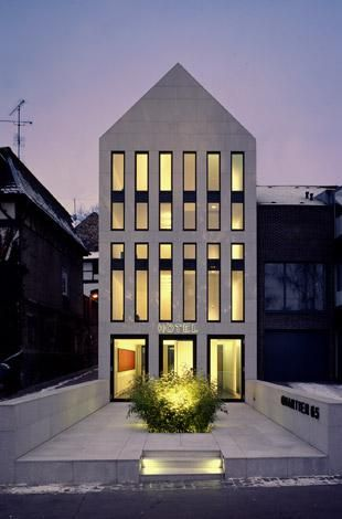 "Max Dudler Architekt, Hotel ""Quartier 65"" Mainz - Elongating the proportion of a stereotypical house to become a hotel?  This has the strange sense of still reading as a house, but feeling like a giant long paper cut out of a house.  How do the windows and doors relate to the ""house"" feel of it?"