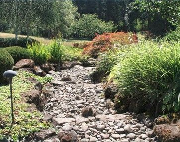 A dry river bed is a great way to break up a boring back yard or a hard to landscape area.