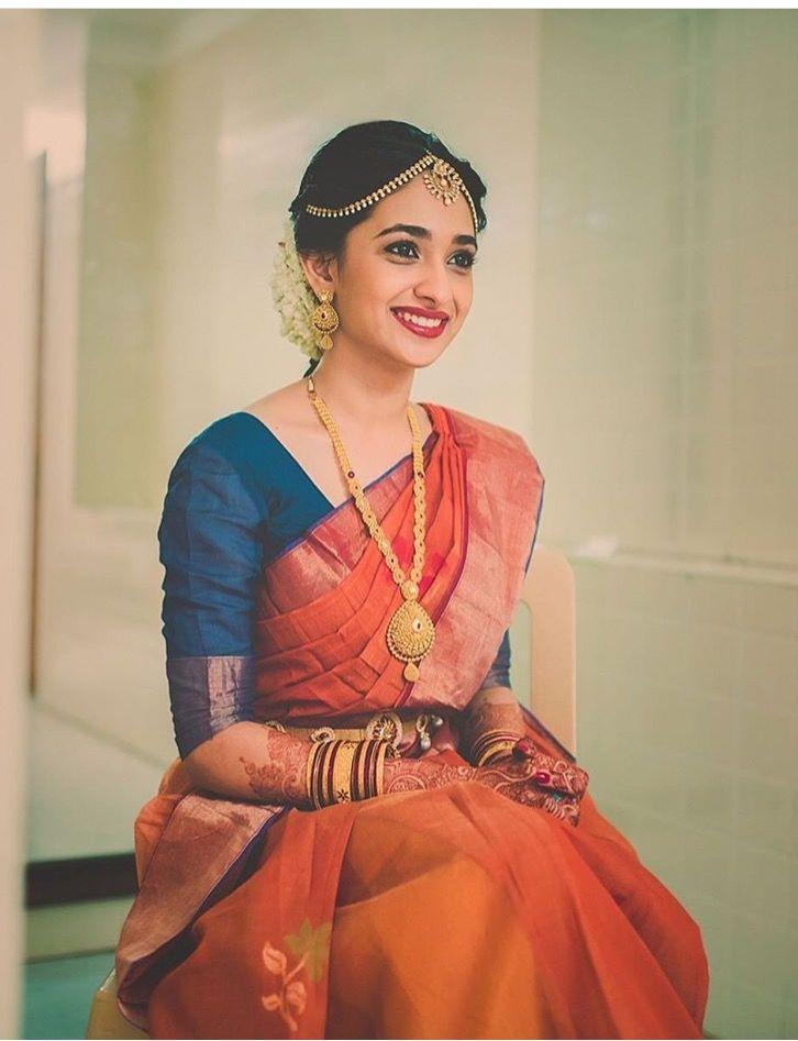 South Indian bride. Gold Indian bridal jewelry.Temple jewelry. Jhumkis. Rust orange silk kanchipuram sari with contrast blue blouse.braid with fresh jasmine flowers. Tamil bride. Telugu bride. Kannada bride. Hindu bride. Malayalee bride.Kerala bride.South Indian wedding.