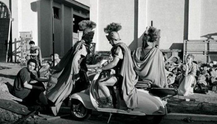 A Roman centurion sits on a Vespa in between takes during the filming of BEN HUR (1958)