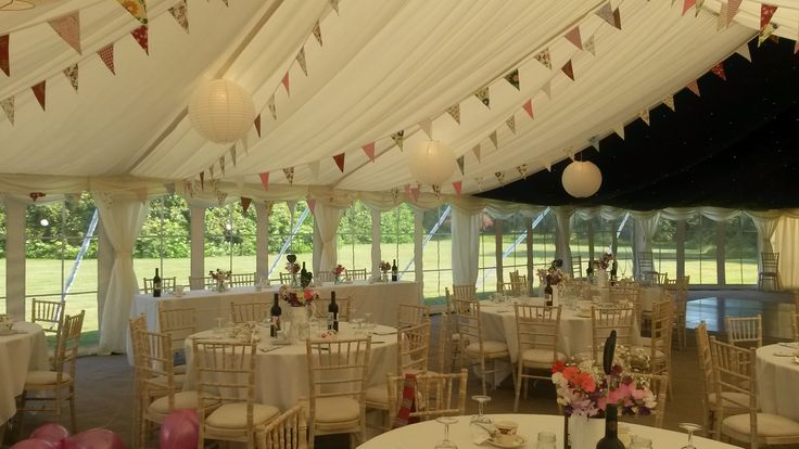 Pretty #bunting and #paper #lanterns hang from the roof in this beautiful wedding marquee.. #summerwedding #marqueewedding