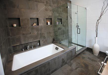 Het heeft een opvallende natuurlijke kleurenmix van warm grijs en helder wit. Voor zowel de vloer, de muur van het ligbad als de zijkanten van het bad is er gekozen voor mooie grijze vierkante tegels met een bijzondere gloed die nog meer een natuurlijk effect geeft.