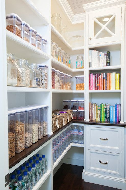 Walk-in pantry features built-in shelving filled with labeled clear food containers, seagrass baskets filled with treats and cookbook shelves