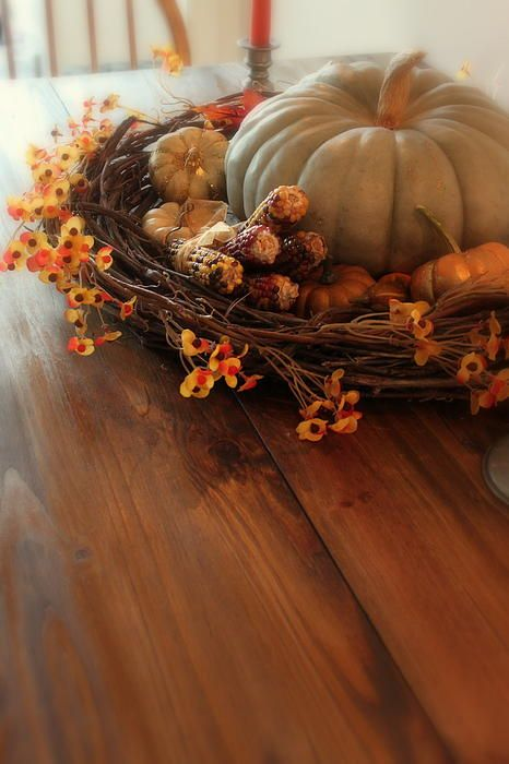 Use a wreath to frame a pumpkin/ gourd centerpiece/fall arrangement.