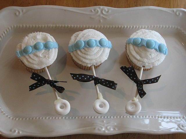 Baby Rattle Cupcakes- would be cute with dumdum lollipops for handles: