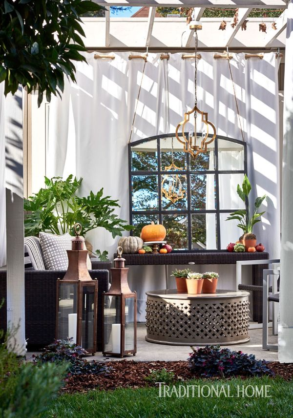 Pumpkins and copper lanterns by Bevolo Gas & Electric Lights serve as the final touches to this delightful outdoor retreat. - Photo: Dustin Peck / Design: Bryan Tapper