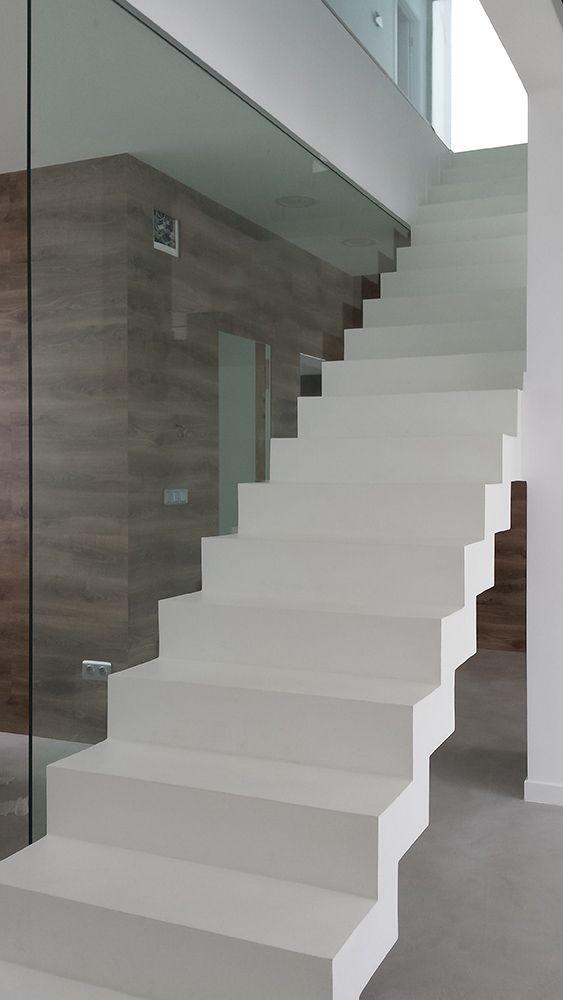 Escalera en el salón de Microcemento con barandilla de cristal