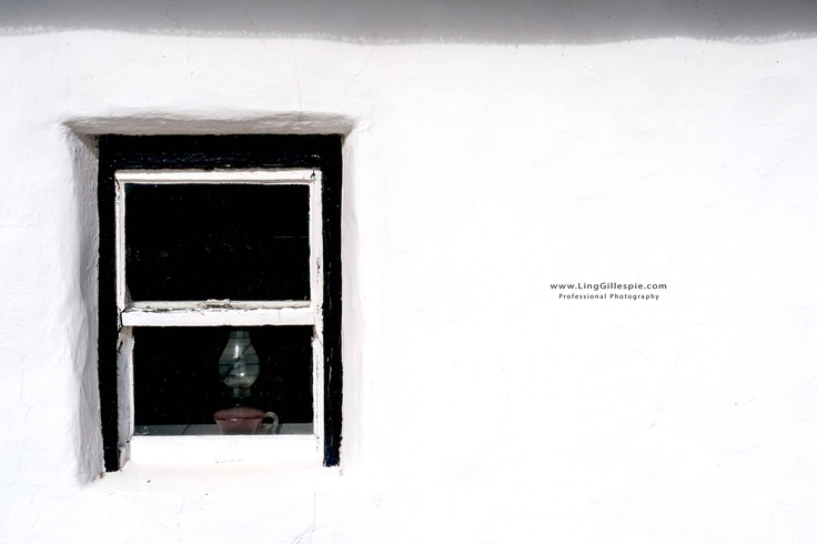white washed cottage window with oil lamp
