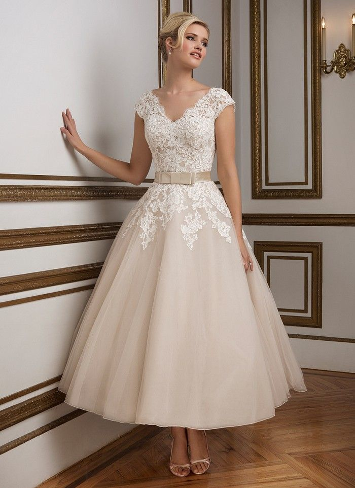 A 1950's vintage inspired V-neckline tulle tea length ball gown rich in hue. Silk Dupion band accented with a bow cinches the waistline for a figure flattering look. https://www.justinalexanderbridal.com/wedding_dresses/8815