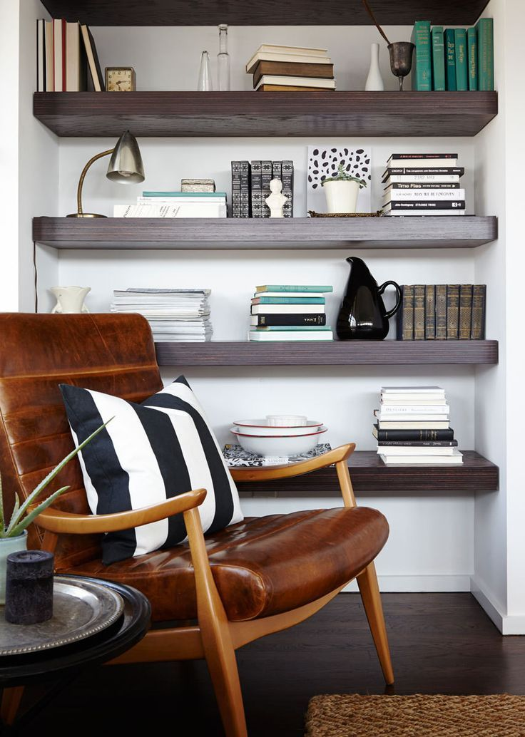 A masculine leather chair keeps company with a floating shelf of vintage treasures.