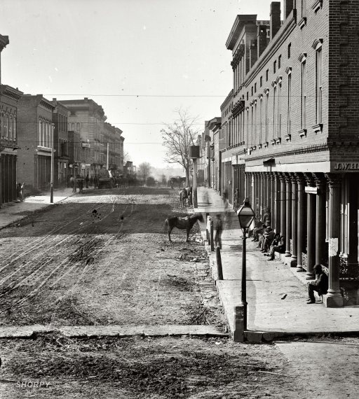 "1864. ""Atlanta, Georgia. Street view."" To the right, a hatter. Everywhere else, dirt and mud. Wet plate glass negative by George N. Barnard."